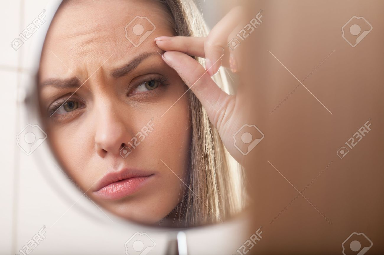 closeup of young woman looking into mirror. mirror reflection of beautiful girl eyebrow - 28561897