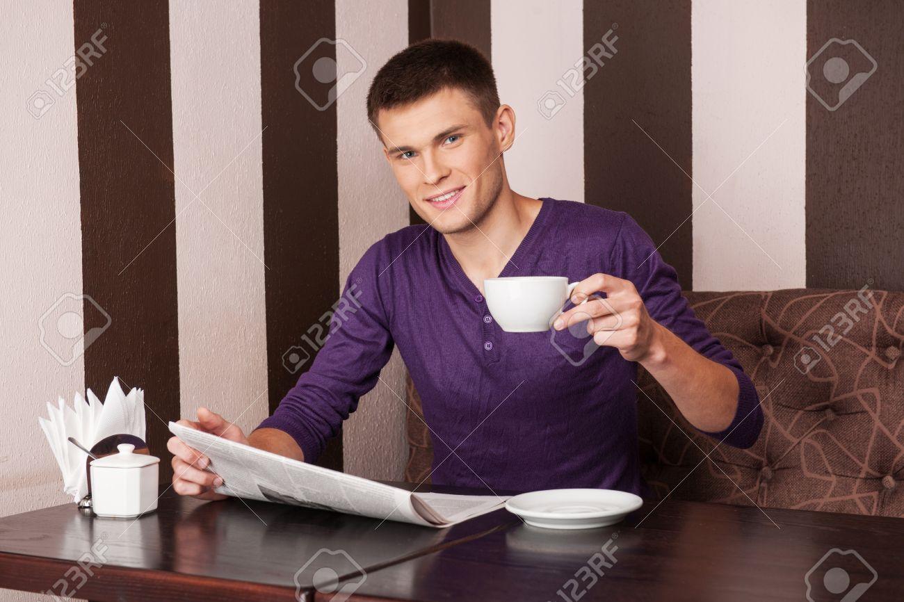 fc17631d7 Joven sentado y tomando café. chico guapo leyendo el periódico en la  cafetería