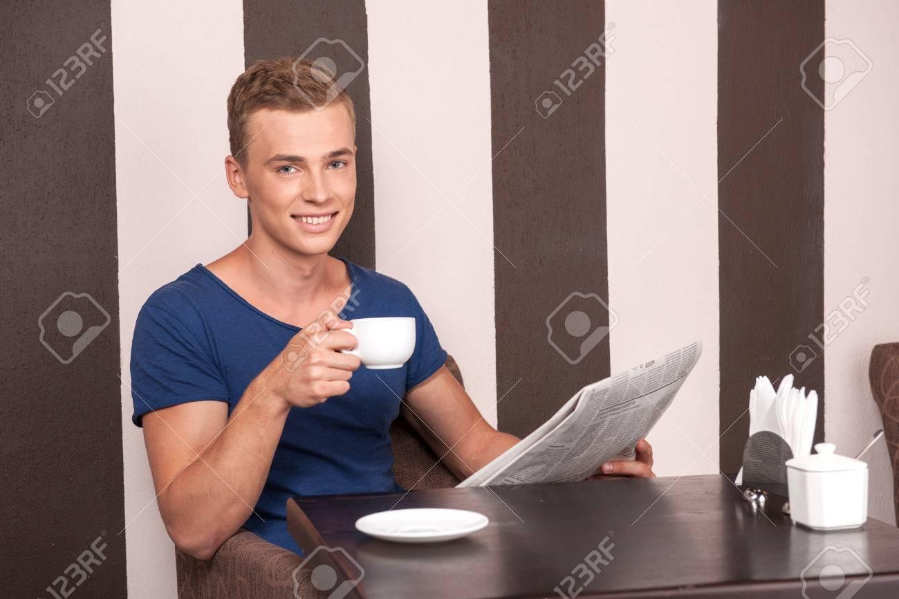 cb79c589d Joven sentado en un café y leyendo. chico guapo leyendo y tomando café