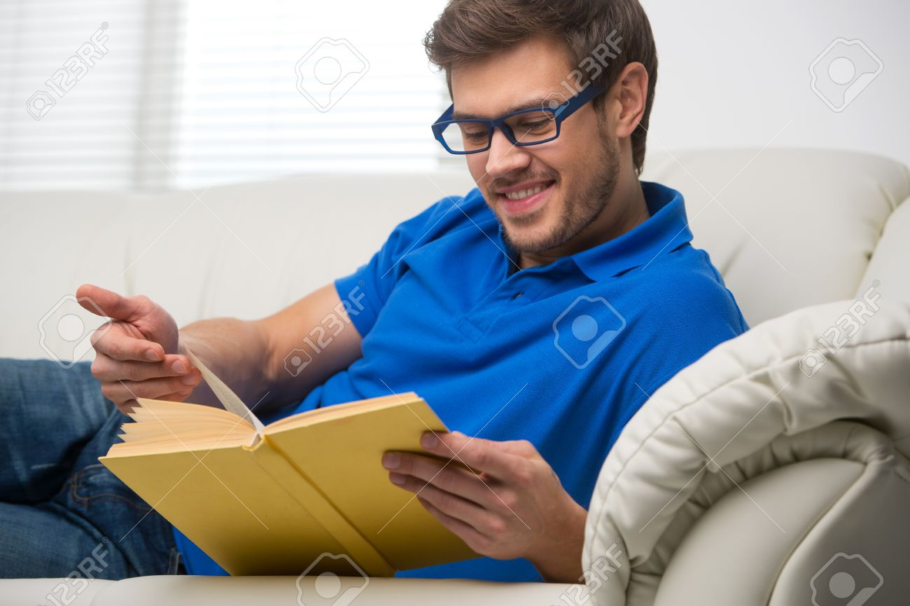 Young Man Stretching Comfortably On Couch. Guy Reading Book And ...