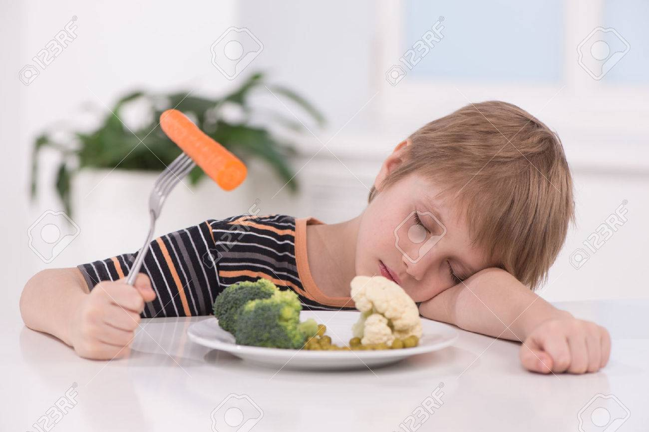 little blond boy eating at kitchen. child holding fork with carrot and sleeping - 31114792