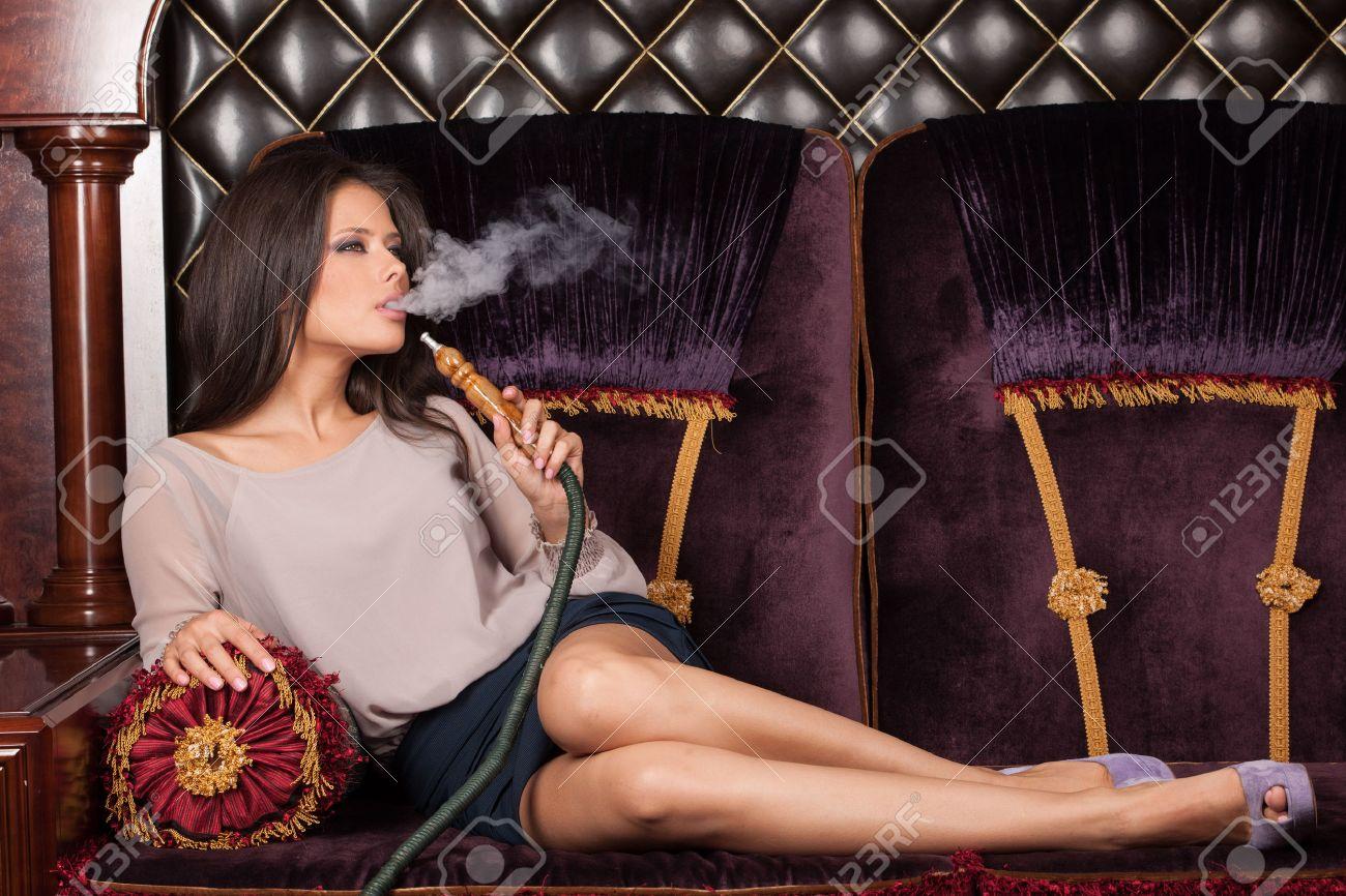 Beautiful young woman inhaling hookah. girl smoking shisha lying on sofa in cafe - 31802605