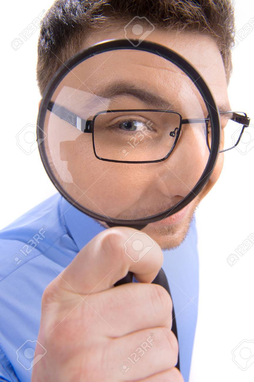 Curious man looking through magnifying glass. portrait of young man looking through magnifying glass over white background - 32001790