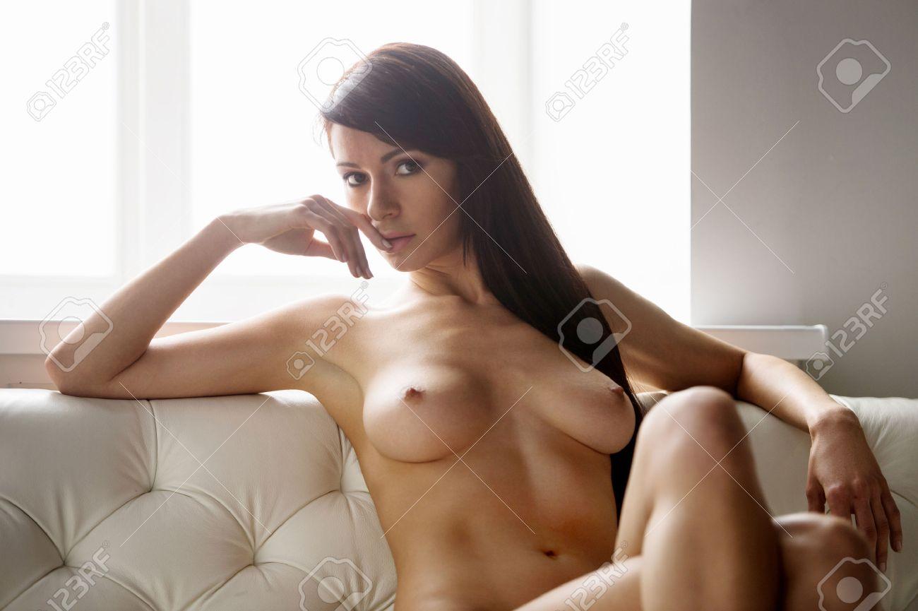 голая брюнетка на белом кожаном диване