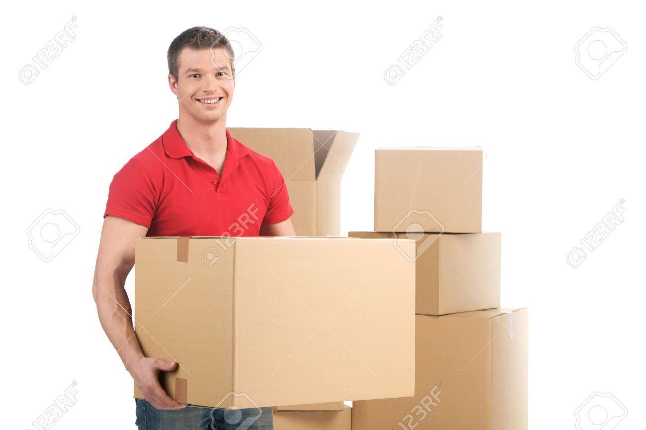man holding moving box and smiling at camera. young man carrying carton boxes - 32577525