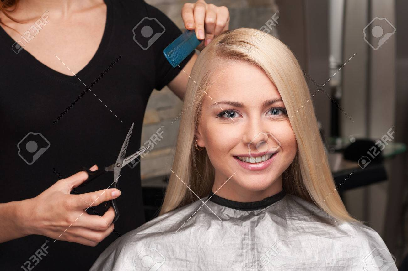 Happy young woman getting new haircut by hairdresser at parlor