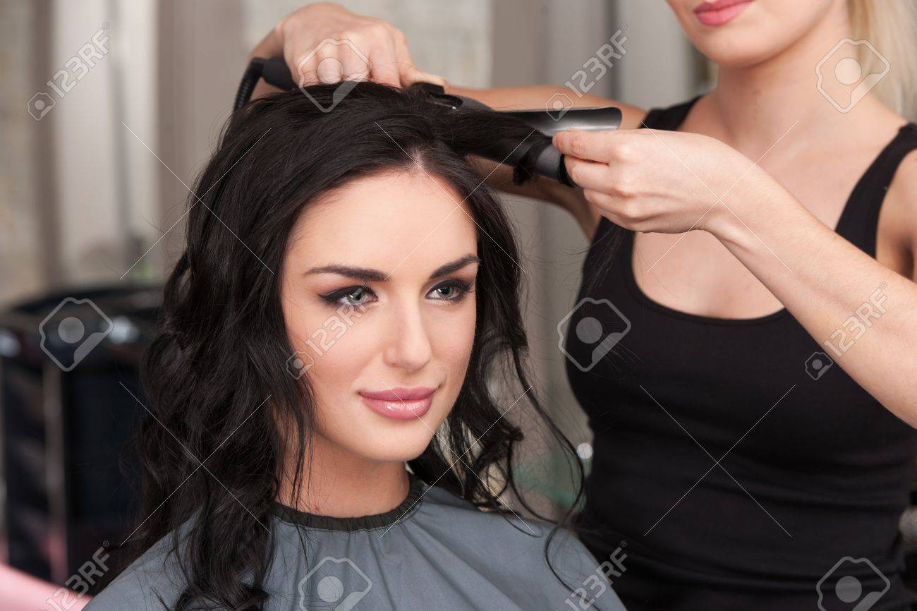 young woman getting her hair curled by stylist at parlor. Beautiful young hairdresser giving new haircut to female - 32577576