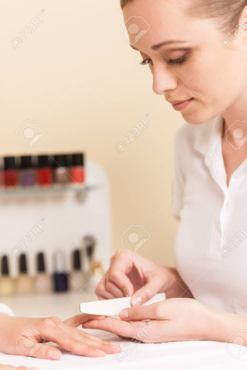 Close-up Of Beautician Hand Filing Nails Of Woman In Salon. manucurist women sitting in spa salon and looking at fingers - 33126057