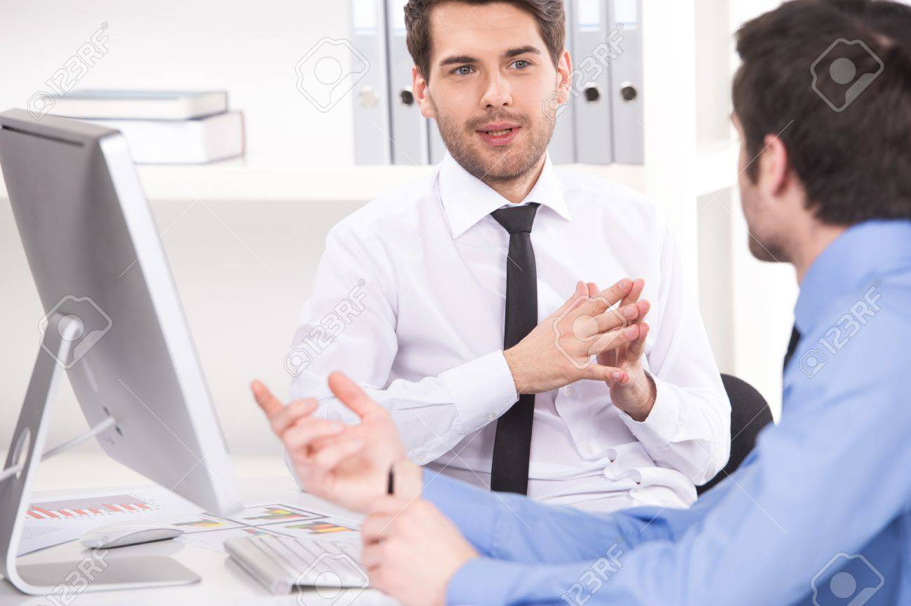 two businessmen having discussion in office. over shoulder view of businessmen looking at each other and using laptop - 33247207