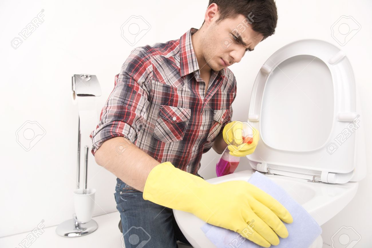 man cleaning toilet with spray cleaner. disappointed guy wiping toilet seat in bathroom - 33484608