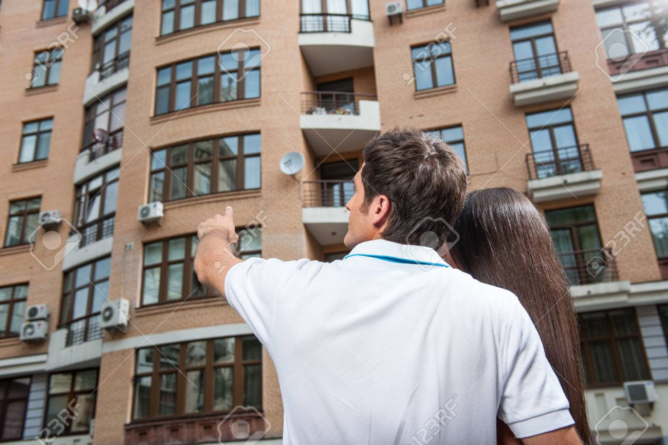 couple standing with their backs towards camera. man pointing to apartment window for brunette woman - 33933210