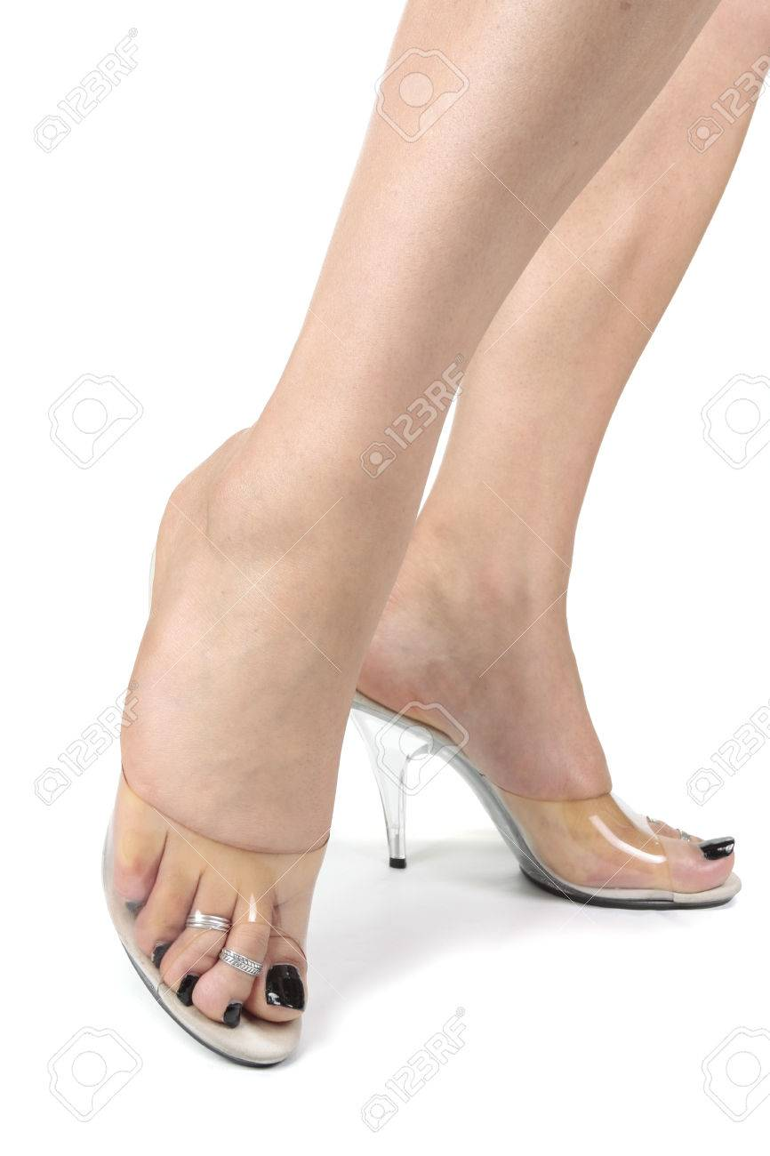 Stock Photo - Woman wearing clear high heel shoes over white background