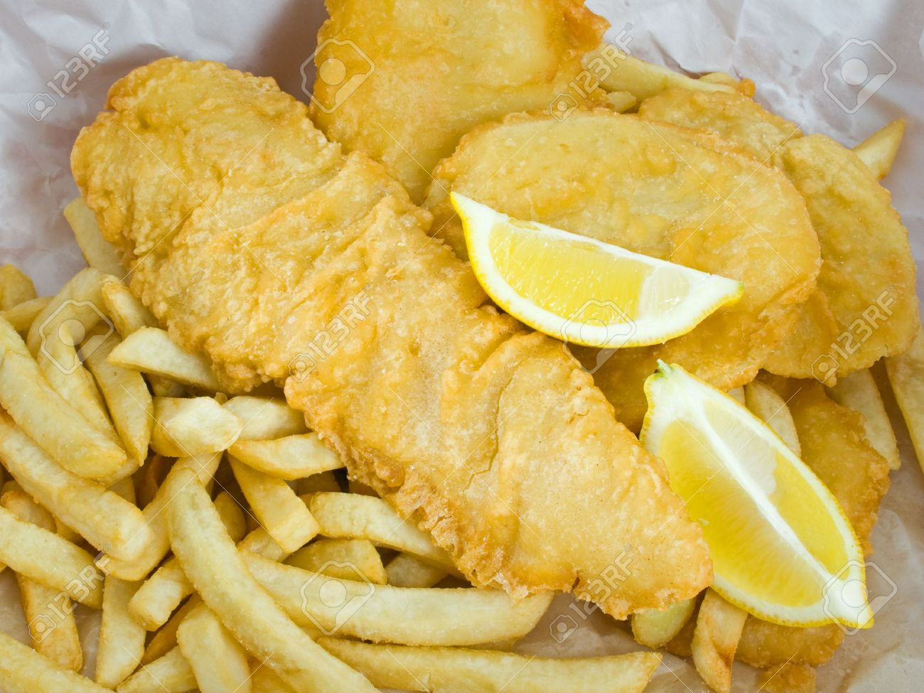 Traditional deep fried fish and chips with lemon in paper wrapping Stock Photo - 3516422