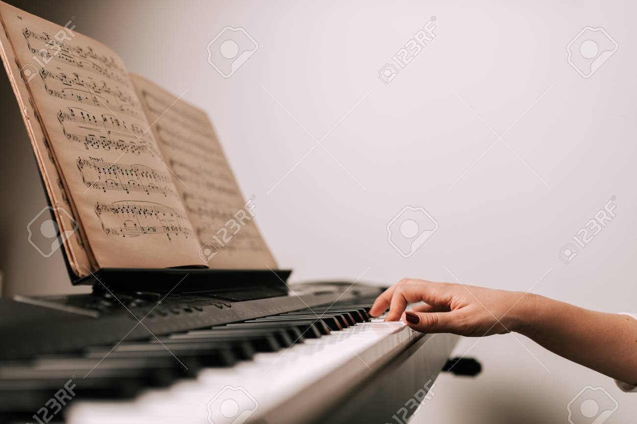 Playing piano from a classical sheet music  Close-up