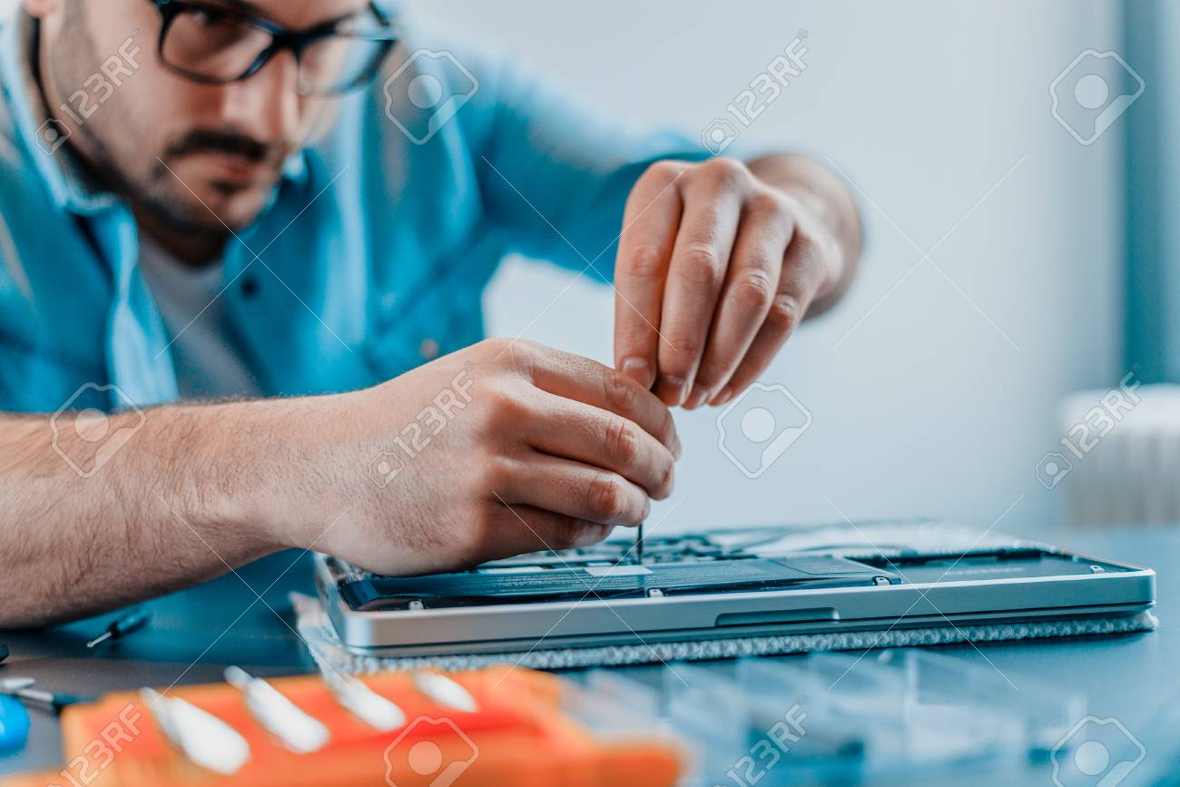 Engineer repairs laptop with screwdriver.Close-up. - 98132353