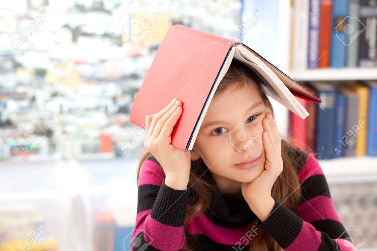 Girl with a book on her head as a symbol for a burnout Stock Photo - 18878679