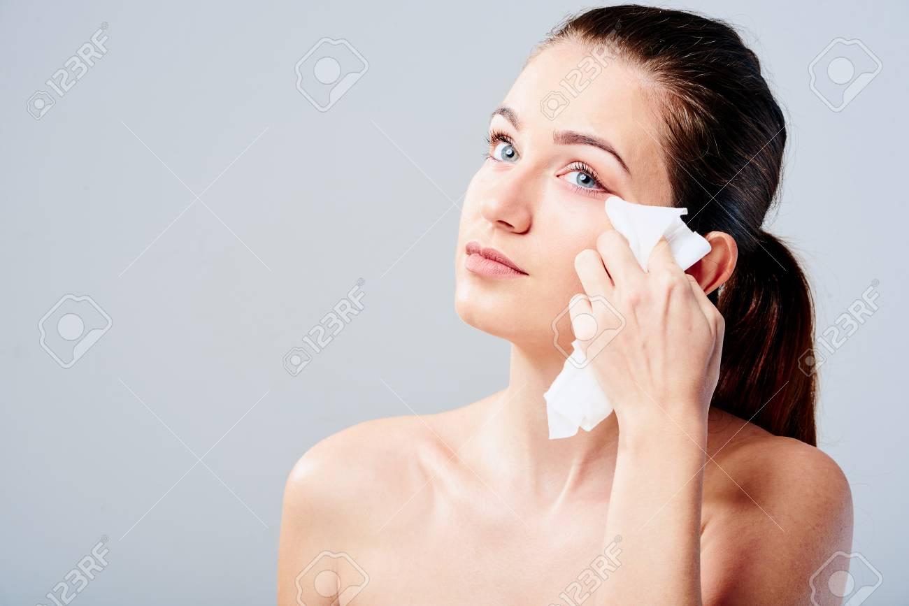 Archivio Fotografico - Portrait of a young brunette woman cleaning her face  with wet wipes. Girl is removing make-up with facial tissues isolated on  grey ... b784458da