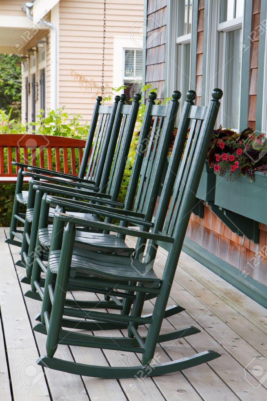 Four green wooden rocking chairs on a porch with partial wood swing Stock Photo - 7565665