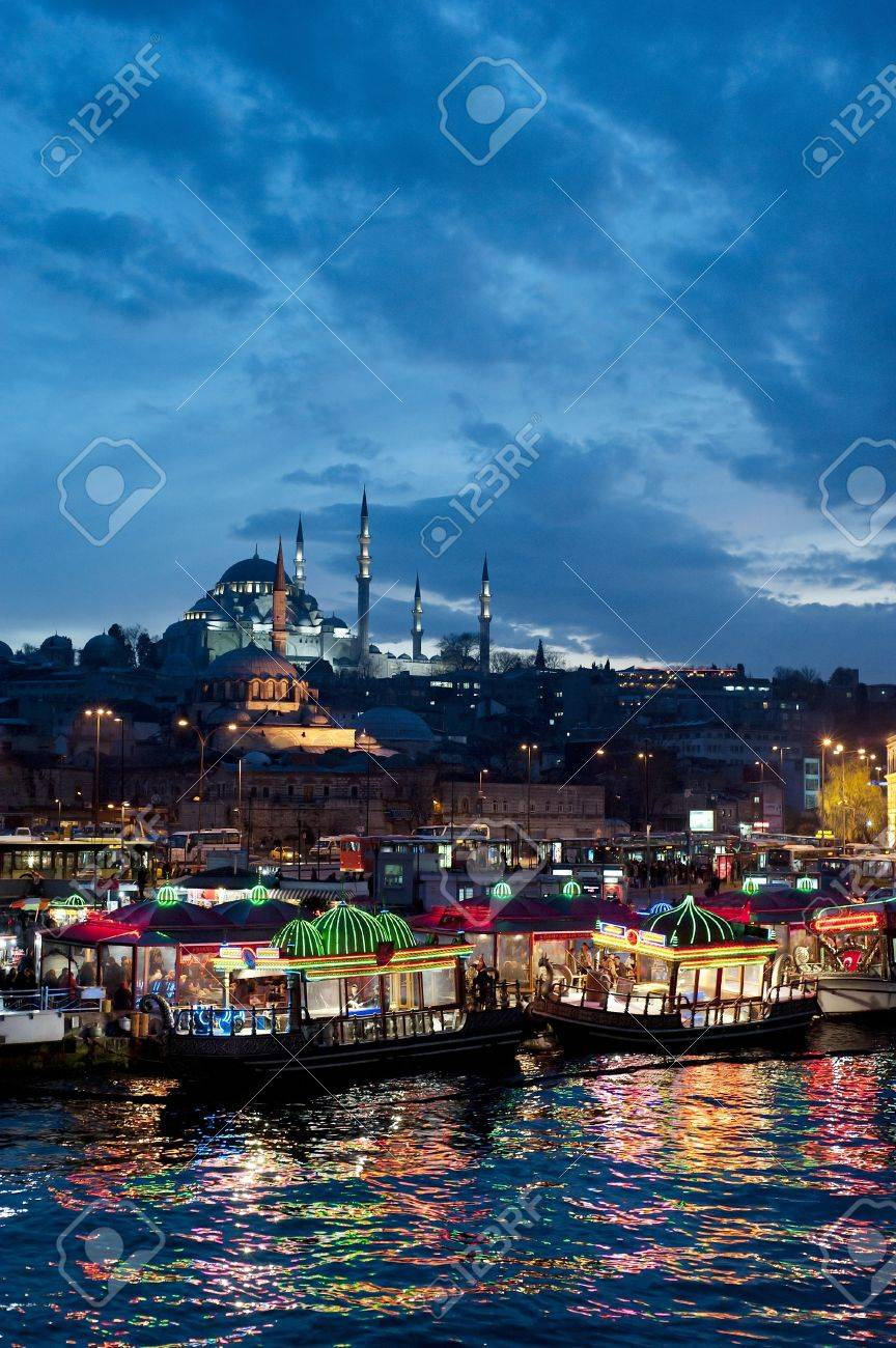Istanbul skyline from Galata bridge by night, with Suleymaniye mosque and fish boat restaurants in Eminonu  Stock Photo - 10447321