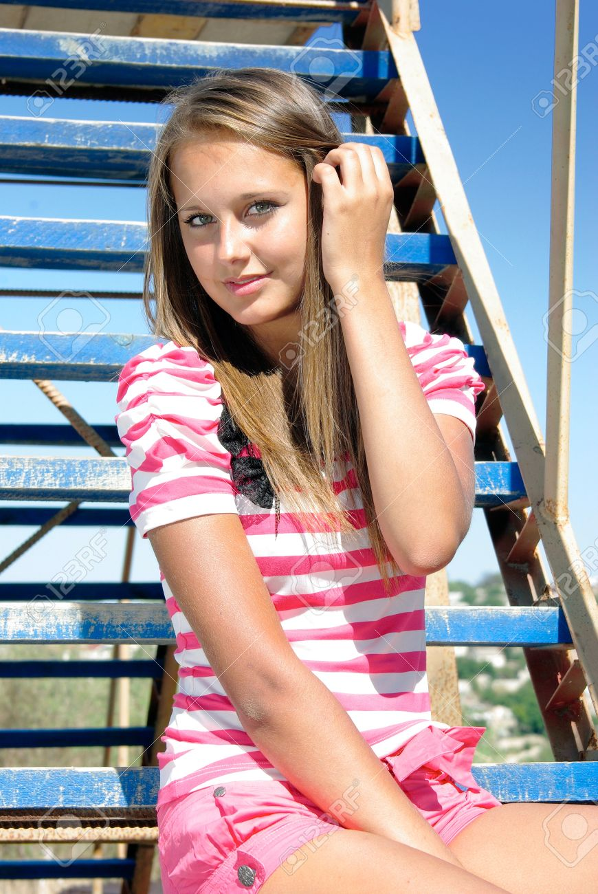 Stock Photo Young Smiling Beauty Sits On A Ladder Over Sky
