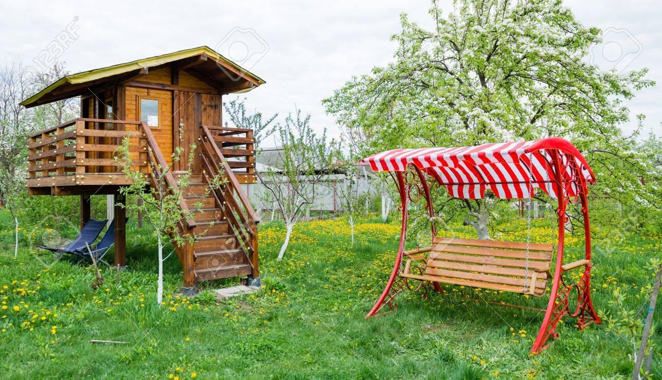 Standard Bild   Swing Bank In Der Nähe Von Kinderhaus Im Garten Mit Bäumen  Und Gras
