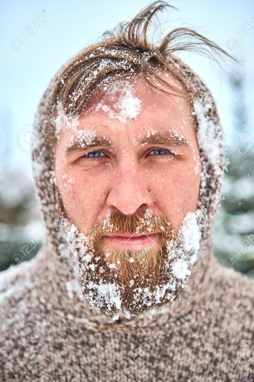 portrait of bearded man with snow on his face man is frozen stock