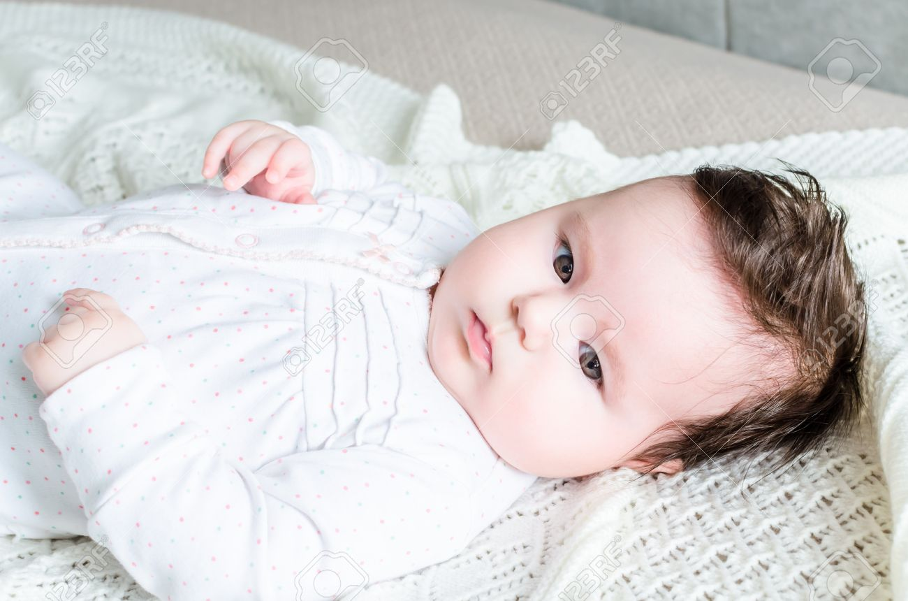 Cute sweet little newborn baby girl with black brunette hair in nice white spotted romper suit looking with big beautiful hazel brown eyes and lying on