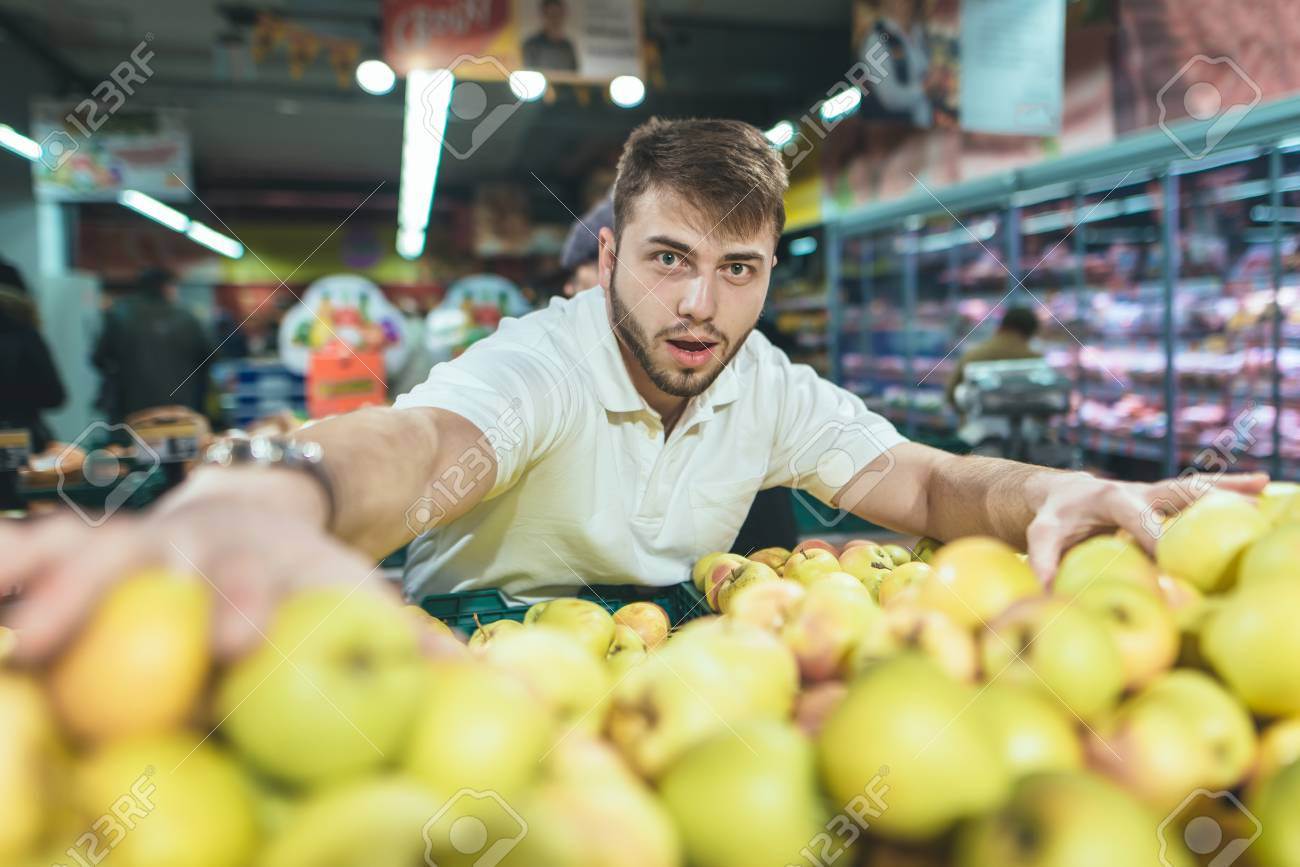 A Funny Man Picks Up Apples In Supermarket And Looks At The Camera Shopping