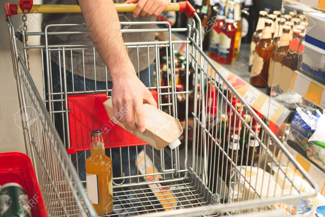 Man's hand puts the products in an empty cart. Buyer makes purchases in a supermarket. Shopping in a supermarket concept. Buys drinks. Hands and cart close-up. Man buys alcohol - 124479001
