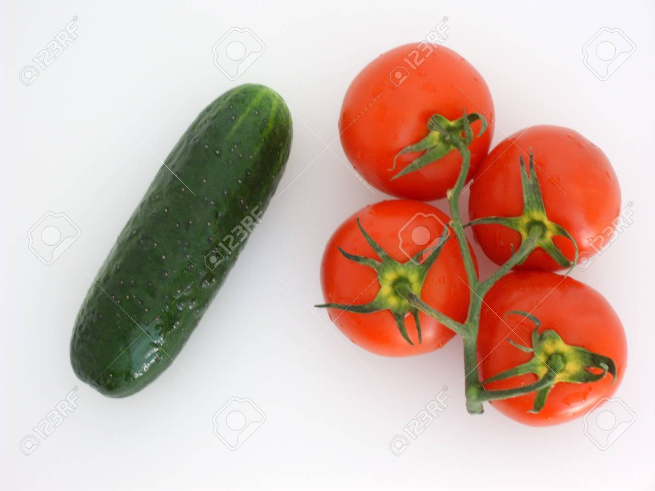 Vegetables: four red tomatoes on a branch and one green cucumber, isolated on white. (stock photo) Stock Photo - 3269265