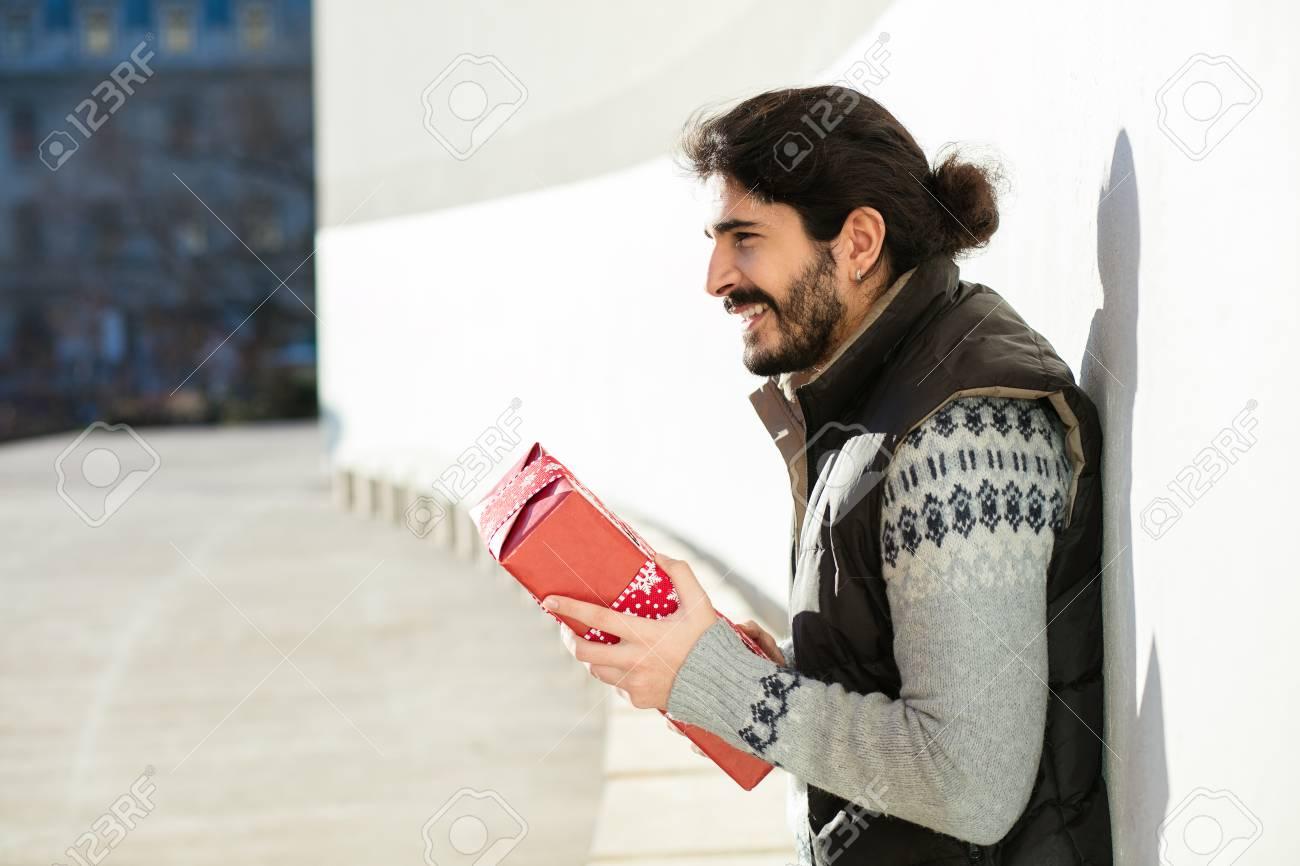 Schöner Mann Mit Langen Haaren Ein Geschenk In Den Händen Denken ...