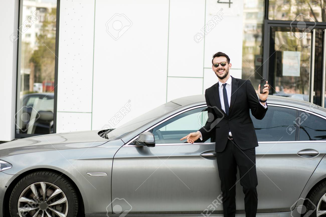 Uber Driver In Elegant Suit In Front Of An Luxury Car Showing