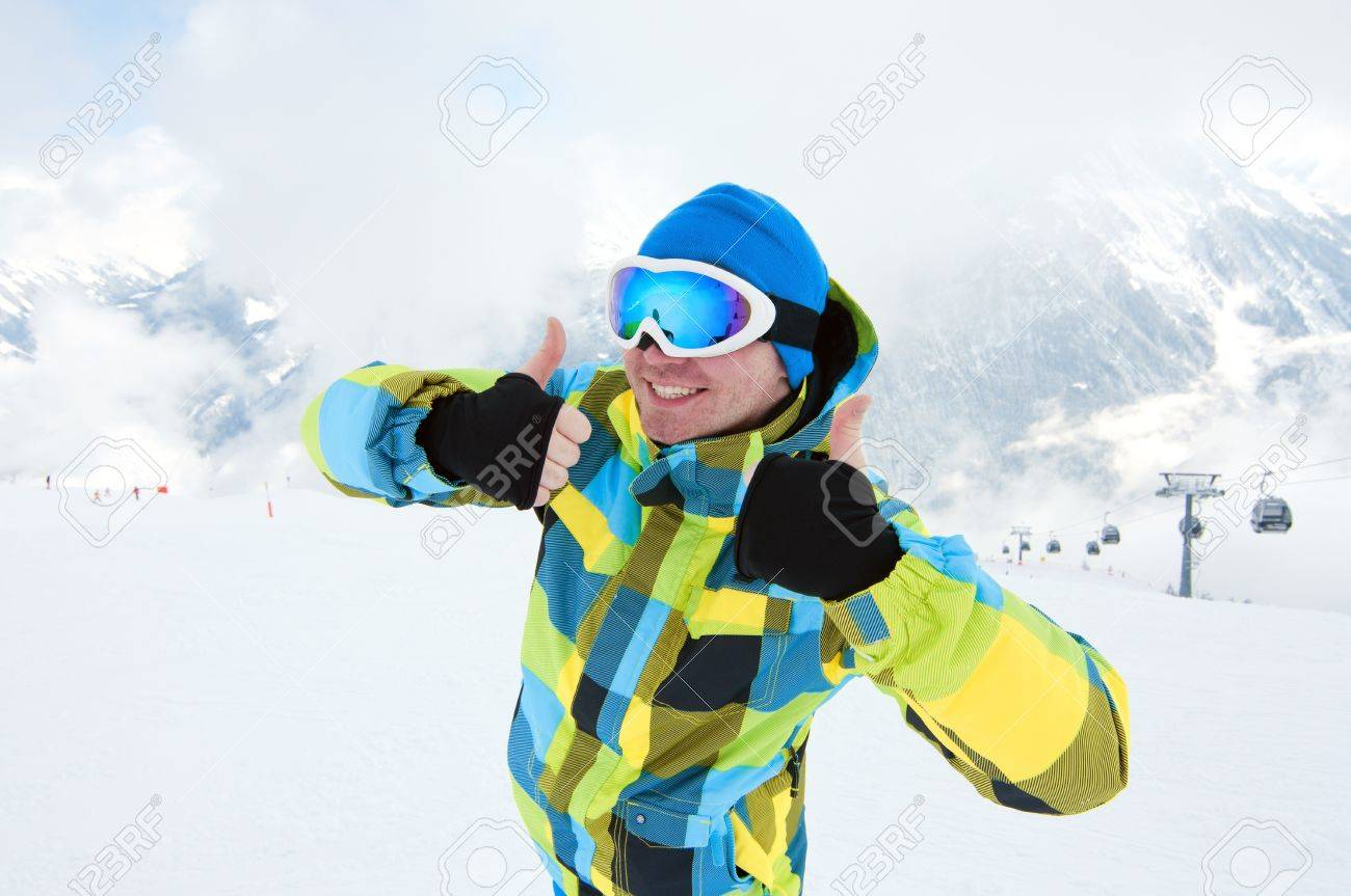 Man wearing ski equipment, smiling on slope with mountains background Stock Photo - 12819668