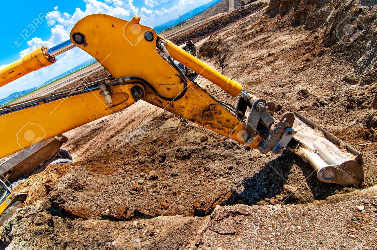 Excavator digging a hole and loading a dumper truck with soil in construction site Stock Photo - 21727929