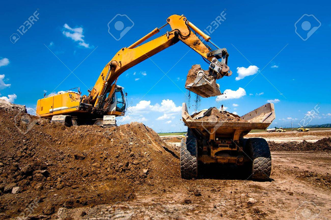 Industrial truck loader excavator moving earth and unloading into a dumper truck - 21727954