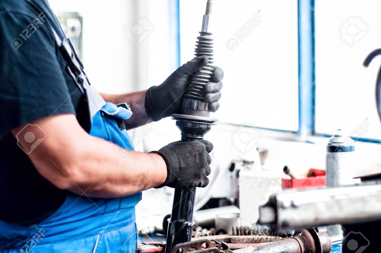 Auto car mechanic working on car shock absorber in car service workshop Stock Photo - 21728041