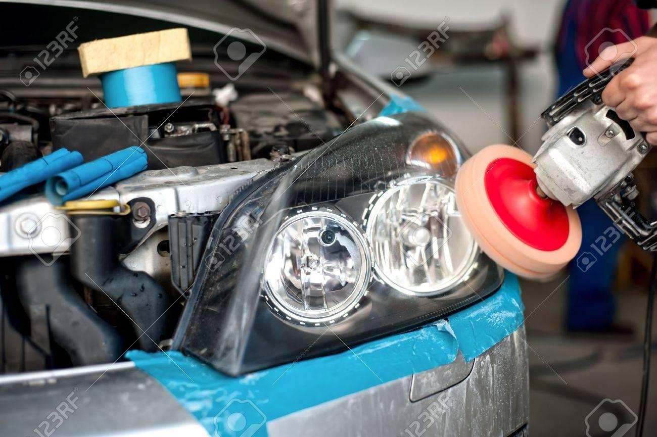 Auto Mechanic Working On Polishing A Car Headlight With Power