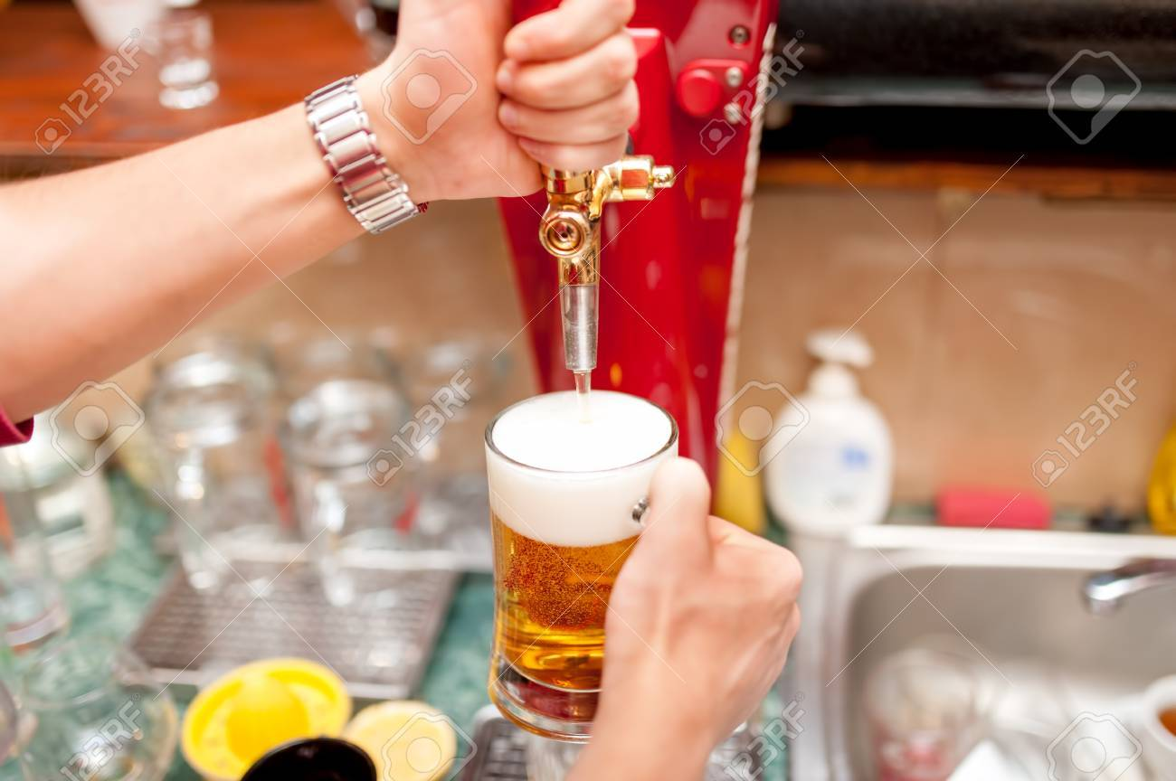 bartender brewing draft beer in pub Stock Photo - 26499553