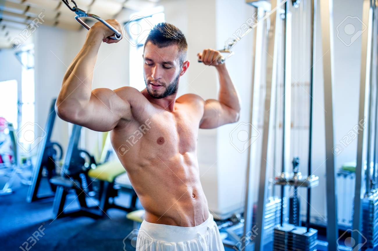 Trainer Bodybuilder Working Out The Biceps And Abs In Gym