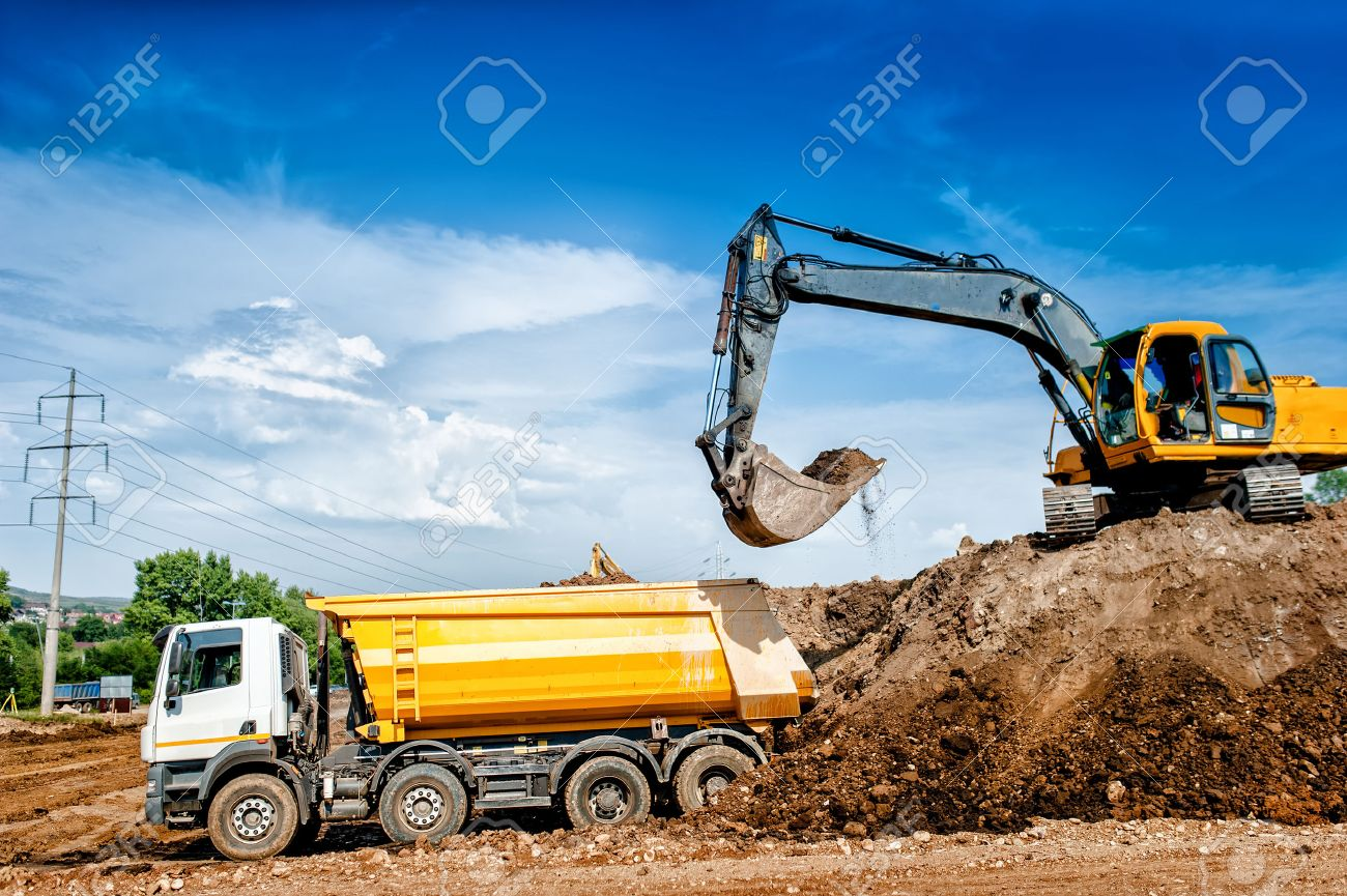 Industrial truck loader excavator and bulldozer moving earth and unloading into a dumper truck stock photo