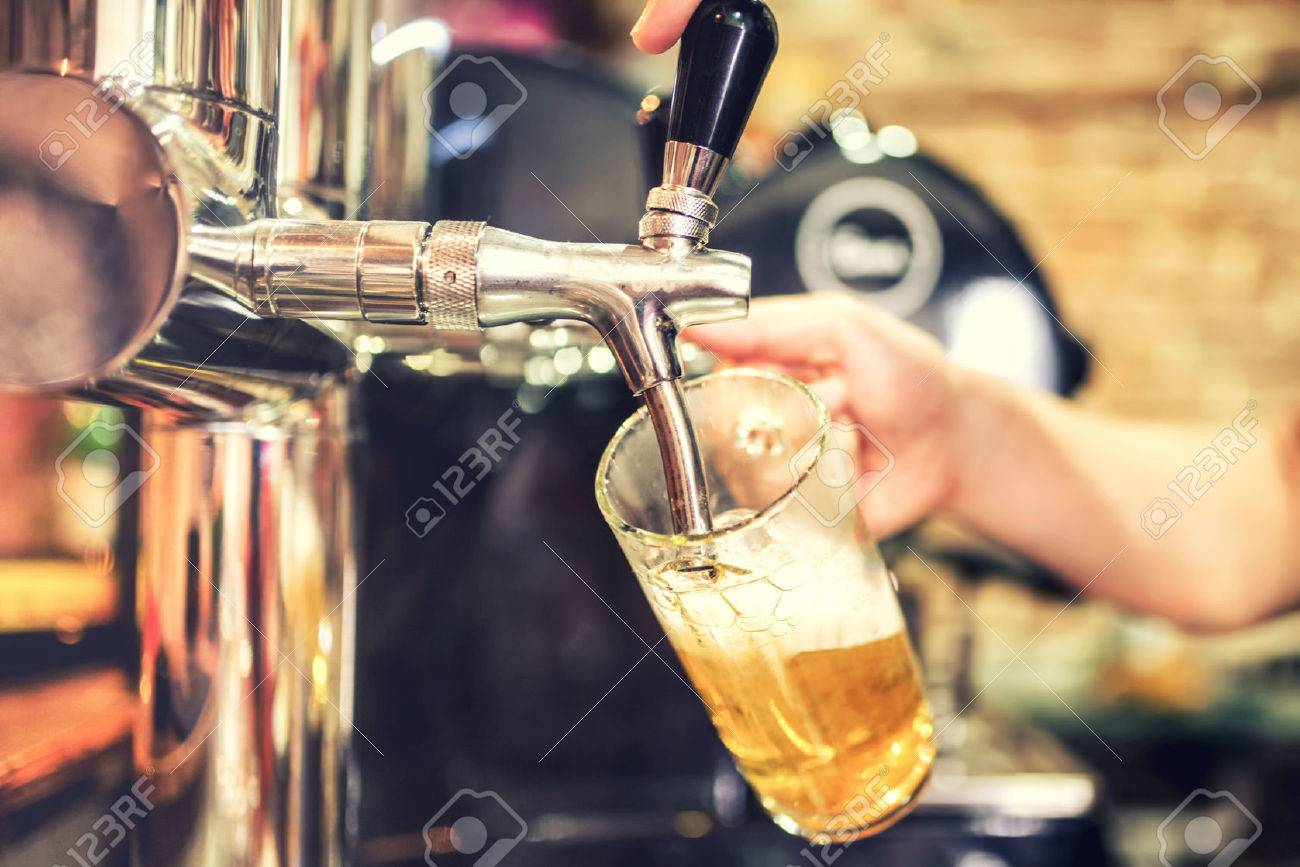 Barman Hand At Beer Tap Pouring A Draught Lager Beer Serving.. Stock ...