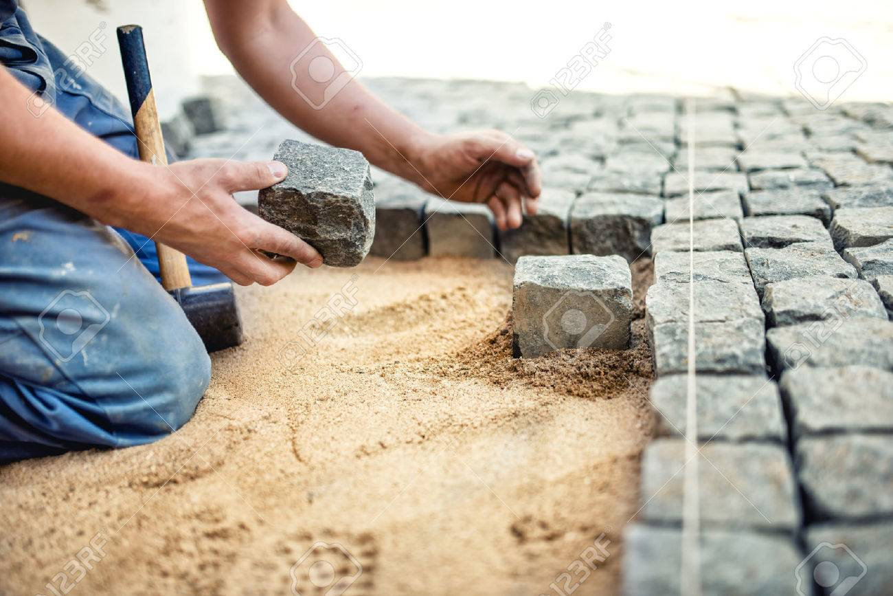 Construction Worker Placing Stone Tiles In Sand For Pavement, Terrace.  Worker Placing Granite Cobblestone