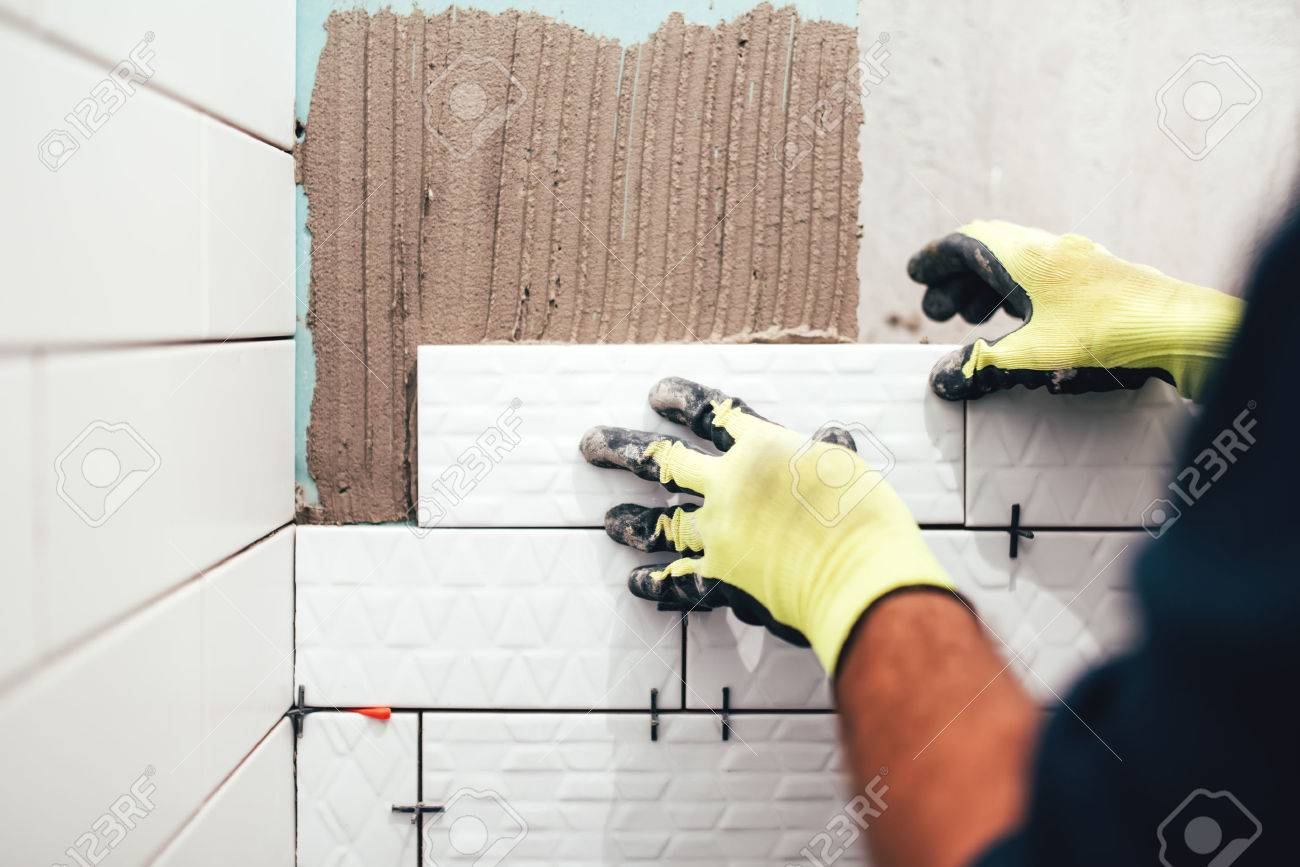 Industrial construction worker installing small ceramic tiles industrial construction worker installing small ceramic tiles on bathroom walls and applying mortar with trowel stock dailygadgetfo Image collections