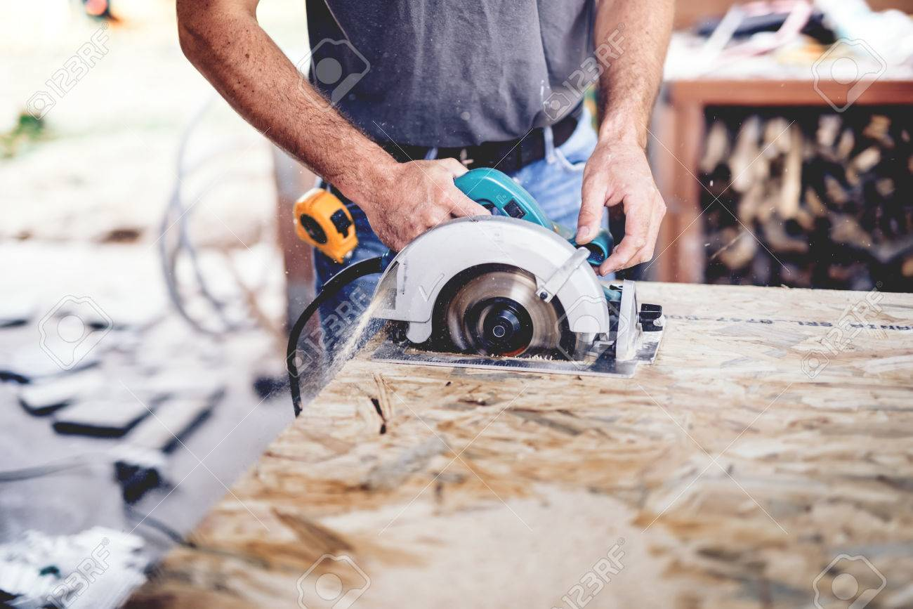 Construction man working with a chop saw in wood workshop  Details