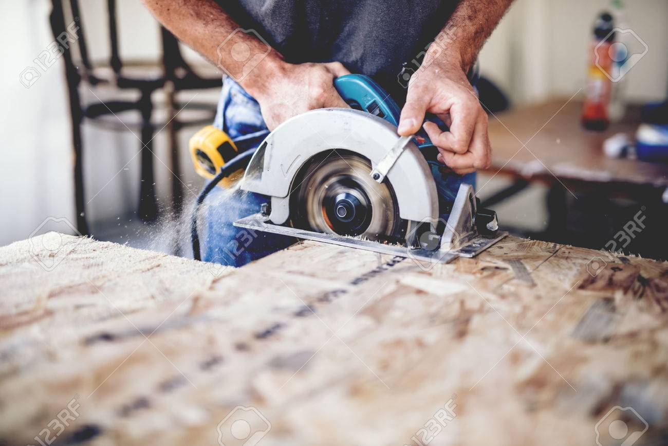 Carpenter using circular saw for cutting wooden boards. Construction details of male worker or handy man with power tools - 70339781