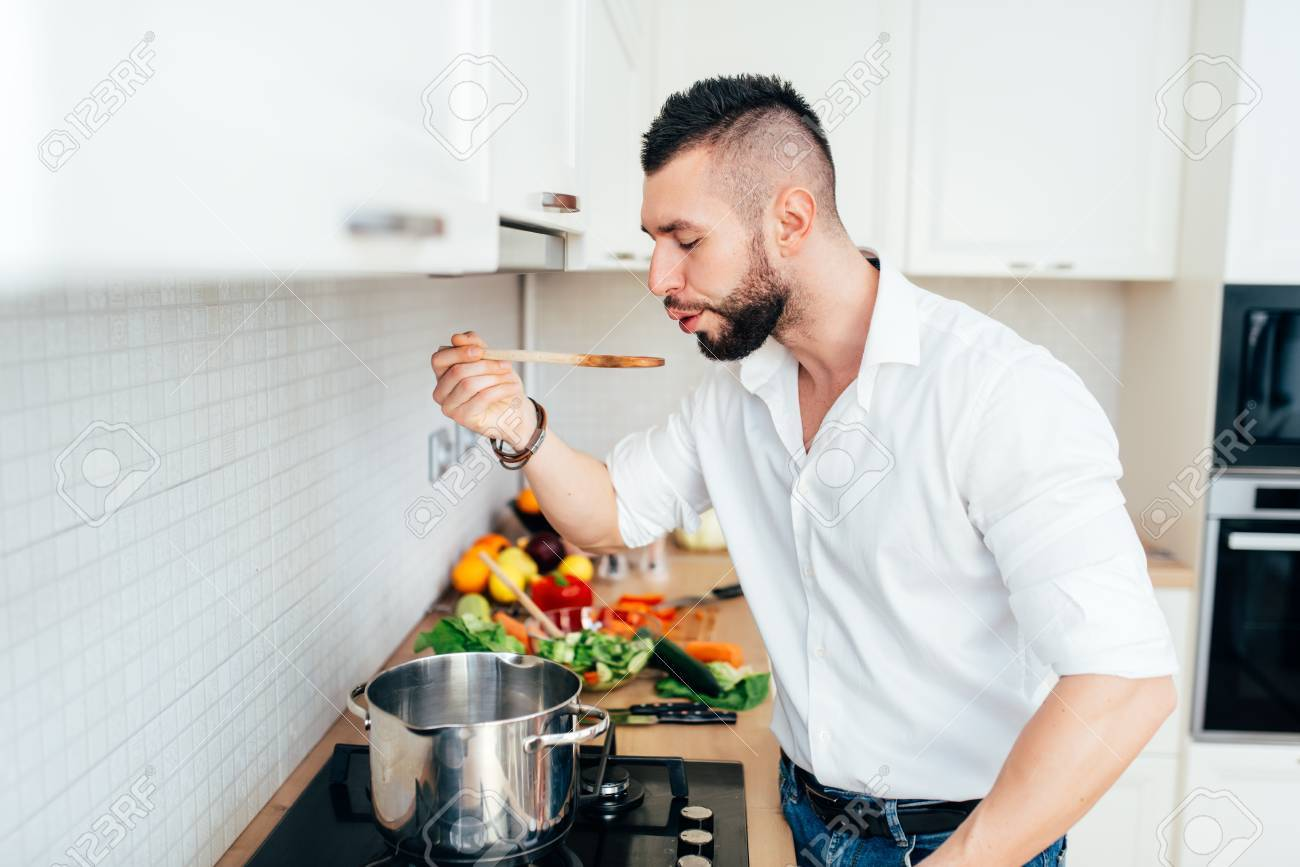 Professional Chef Cooking In White Kitchen, Tasting And Adding ...