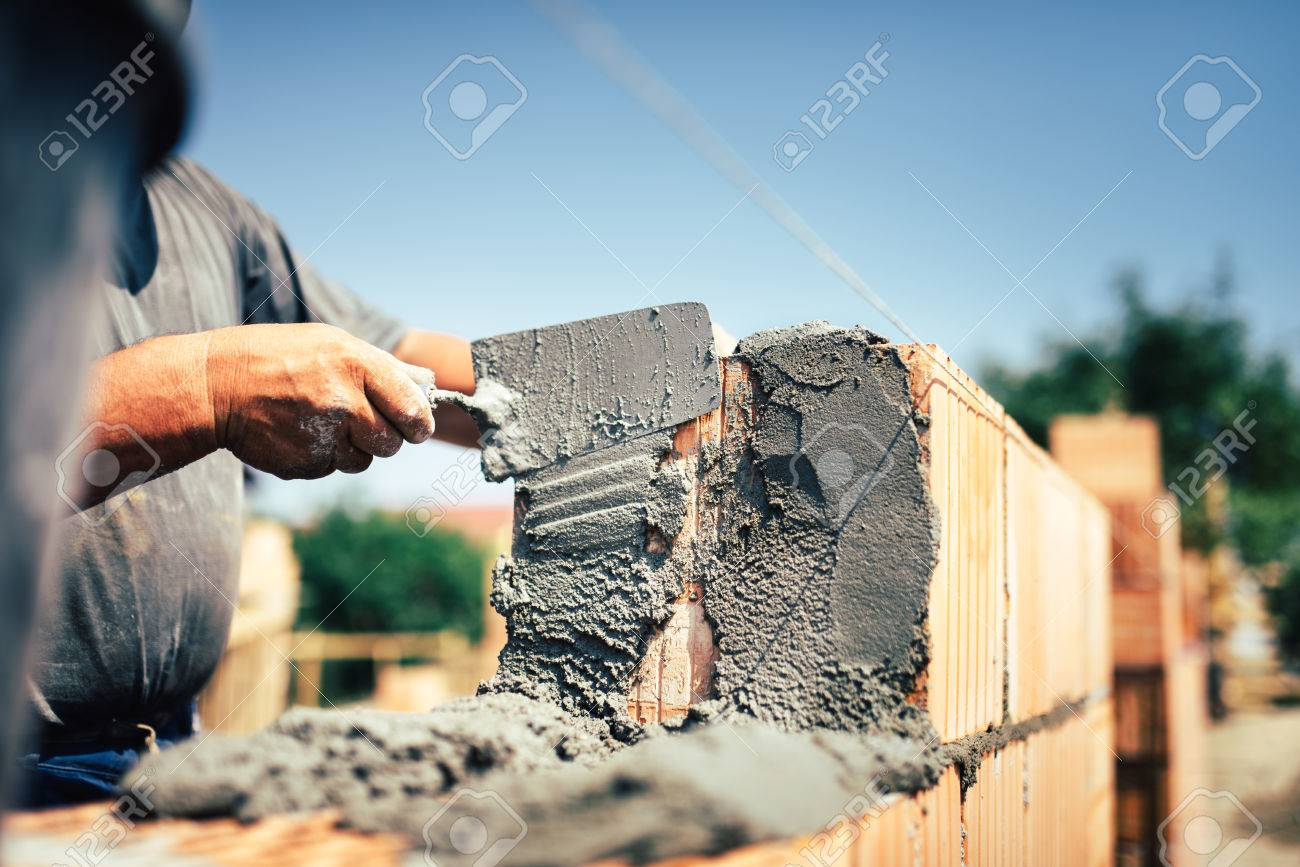 Bricklayer construction worker installing brick masonry on exterior wall with trowel putty knife - 71990920