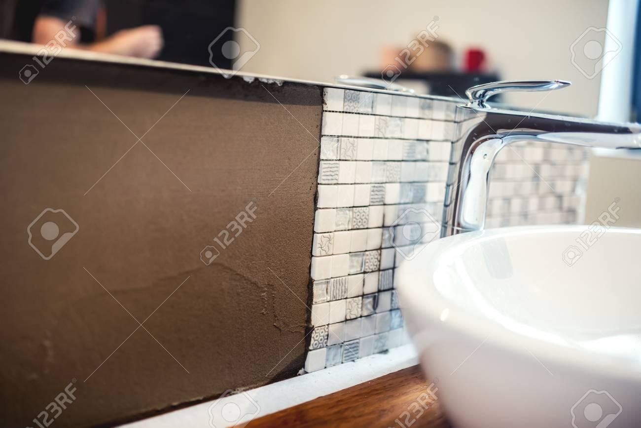 Fermer les détails des travaux de rénovation. Détails de la salle de bain  avec carreaux de mosaïque et colle à base de ciment