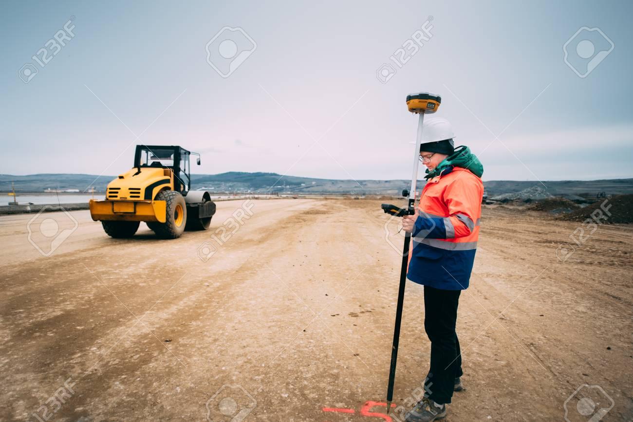 Portrait of engineer on construction site, surveyor using gps