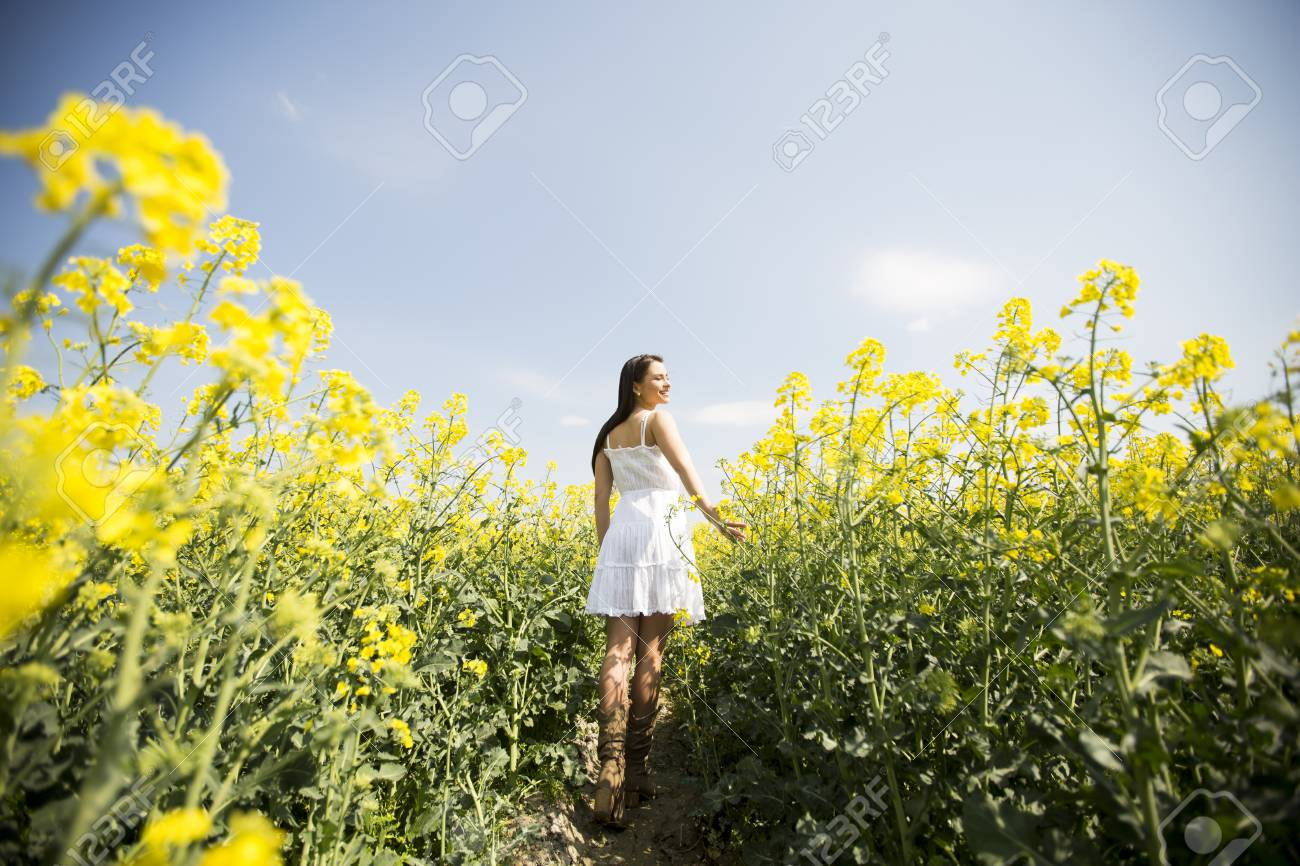 Young Woman Standing In A Field Of Yellow Flowers On A Sunny Stock